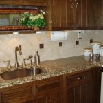 elegant white groutless backsplash design above cream patterned marble top on wooden cabinetry with transparent storage with modern sink