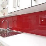 exotic red glossy acrylic backsplash design in modern kitchen idea with white upper cabinetry and white drawesr for main cabinet with double sinks and curved faucet