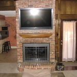 fireplace mantel height on brick wall with flat tv above the fireplace and rug on floor near the kitchen island