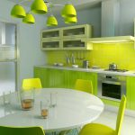 fresh and luxurious green kitchen design with transparent cabinet and green cabinet and green acrylic backsplash with round white dining table and green cahirs and vault pendants