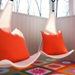 fresh chairs that hang from ceiling with comfy decorative cushions and cheerful carpet and flower pot