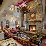 giant fireplace design made of stone with rustic cedar decoration with round vintage chandelier with boho sofa design and rustic coffee table with patterned area rug