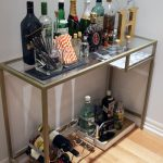 glass top gold bar carts ikea with bottles of wine and beer plus straws and alphabetical arts on wooden floor and white wall