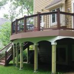 Gorgeous Arched Porch Design With Brown Fencing Idea With White Porch Skirting With Wooden Staircase Upon Grassy Meadow