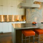gorgeous kitchen island idea with orange stools beneath smokestack with induction stove and white cabinetry with stunning modern lighting