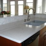 gorgeous modern kitchen design with large glass window with natural wooden cabinetry with cashemere white granite with curved faucet