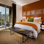 gorgeous orange bedroom design with mounted palette and wooden white end table with lamp and orange bed sheet and bench and gorgeous area rug