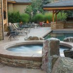gorgeous stony built in hot tub design with decorative stone and concrete patio with seating and free standing lanterns