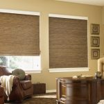 graber blinds review in natural material on glass windows in living room with brown leather armchair plus wooden sideboard and modern rug plus framed painting