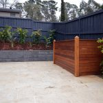 hidden pump pool equipment enclosures from solid wooden fence and black fence plus garden at the corner of backyard
