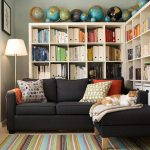 home library deisgn by Better Homes and Gardens with L shape rack black sectional sofa with one chaise multiple colored pillows a collection of globes standing lamp colorful stripes pattern rug