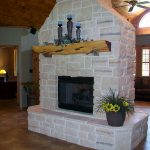 home shaped fireplace design in white brick style with cedar decoration with cream flooring and potted plant with ceiling fan