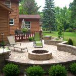 house design with lush vegeatation and round paved patio design with in ground fire pit with reclining chair with shrub