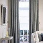 inverted pleat drapes in gray with mirror and wooden end table plus candle holder and wooden flooring plus white comfy armchairs
