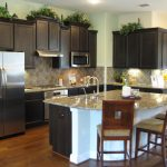 large kitchen islands with seating and storage plus granite countertop and black wooden kitchen cabinets plus comfy dining chairs and wooden floor