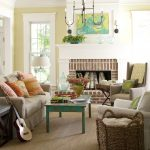 light cream sofa with orange pillows a white corner chair with green pillow a brown corner chair with green pillow green shabby look coffee table  red bricks fireplace frame and white fireplace mantel