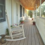 lounge of front porch with a pair of rocking chairs in white tone and white vertical wood railing plus wood planks floors