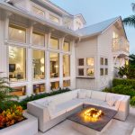 luxurious outdoor patio in Key West style L shape white sofa with pillows square fire pit table white ceramic tiles floors for patio's floors large built in concrete planters