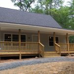 medium size front porch in a ranch construction with vertical wood rails system and log pillars and outdoor wood stairs plus its rails