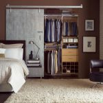 metal sliding barn doors for closets with shelf and hanging rods and shoes storage in small bedroom with divan bed and nightstand plus rug on wooden floor