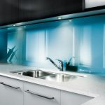 modern and minimalist kitchen design with sophisticated white cabinetry with drawers and stain holder with soft blue acrylic backsplash