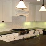 modern cabinet lighting design with groutless brick backsplash idea beneath white wooden cabinetry with black top with modern island and curved faucet beneath vault pendants
