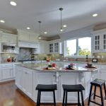 modern large kitchen islands with seating and storage with white kitchen cabinets plus pendant lighting plus wooden floor and black wooden stool
