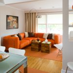 modern minimalist living room furniture in bright orange color with white and brown colored pillows natural wood stump coffee tables permanent shelves as room partition orange rubber rug for wood floors