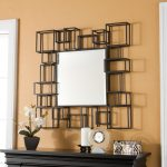 modern sheffield home mirrors  with unique black frame and wooden console table with flower vase and candle holder plus alarm clock on pastel wall paint scheme