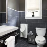 modern white residential urinal in men's bathroom with grey brick pattern wall and floor plus toilet and bathroom vanity unit plus sink and towel holder