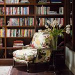 most comfortable reading chair with floral pattern plus round wooden end table with flower vase decorated with wooden bookshelf and hardwood floor