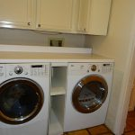 Multipurpose Cabinet Design For Washer And Dryer With Double Machine Upon Brown Tile Flooring Design Bathed In Dull White Tone
