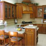 natural brown stained wood kitchen cabinets  glass door top cabinets white marble kitchen countertop united with kitchen island  a sink and faucet in kitchen island  two wood bar chairs