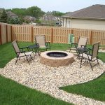 natural pebble patio design with in ground fire pit with reclining chairs around grassy meadow with wooden fence