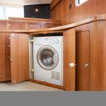 natural wooden boxes washer dryer cabinet design with slapper doors beneath wooden wall upon white flooring idea
