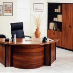 natural wooden u shaped desk design with tall backrested swivel chair aside large and tall cupboard with wall photo gallery