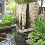 outdoor small landscape with koi ponds with wooden deck and greenery and tall wall beneath shady tree