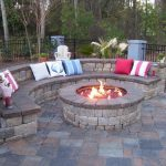 paved patio design with in ground fire put with half concrete bench design with colorful cushions beneath trees