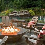 paved patio design with wooden deck lawn chair with round in ground fire pit with red white stripe patterned cushions aside lake