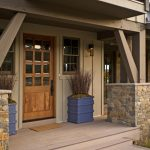 porch construction in a ranch style home with a pair of concrete planter boxes in blue color log pillars with natural stones base a security screen and storm door as the main entrance