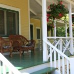 porch design for country ranch homes with a pair of rattan chairs some hanging decorative plants white painted wood railing system for porch green vinyl floors for porch
