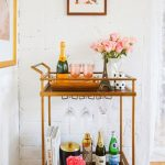 pretty metal and wooden bar carts ikea with rose vases and eiffel ornament plus wine and glass plus books and wooden floor with picture on white wall