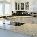 price of granite countertops in white with wooden cabinets plus sink and black tile backsplash in brick pattern and glass windows