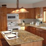 price of granite countertops with classic pendant lamps plus kitchen island with wooden seating plus fruit basket that hang on ceiling