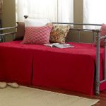 queen size daybed frame with unique trundle frame and red comforter and pretty decorative cushion with beige rug on wooden laminate floor