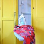 red cloth with iron upon white ironing board idea inside yellow storage cabinet with metal holder