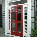 red framed and trimmed screen door with transparent glass panel two sidelights with window blinds an entryway mat grey wood planks walls and floors