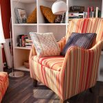 retro stripped orange reading chair for bedroom with comfy cushions and bookshelves and standing lamp plus wooden floor