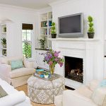 room design with white fireplace mantel and white sofa series plus their pillows wall mount TV set built in books shelves and brown rug designed by Better Homes and Gardens