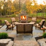 round paved outdoor patio design with cream armchairs with fireplace with grassy meadow